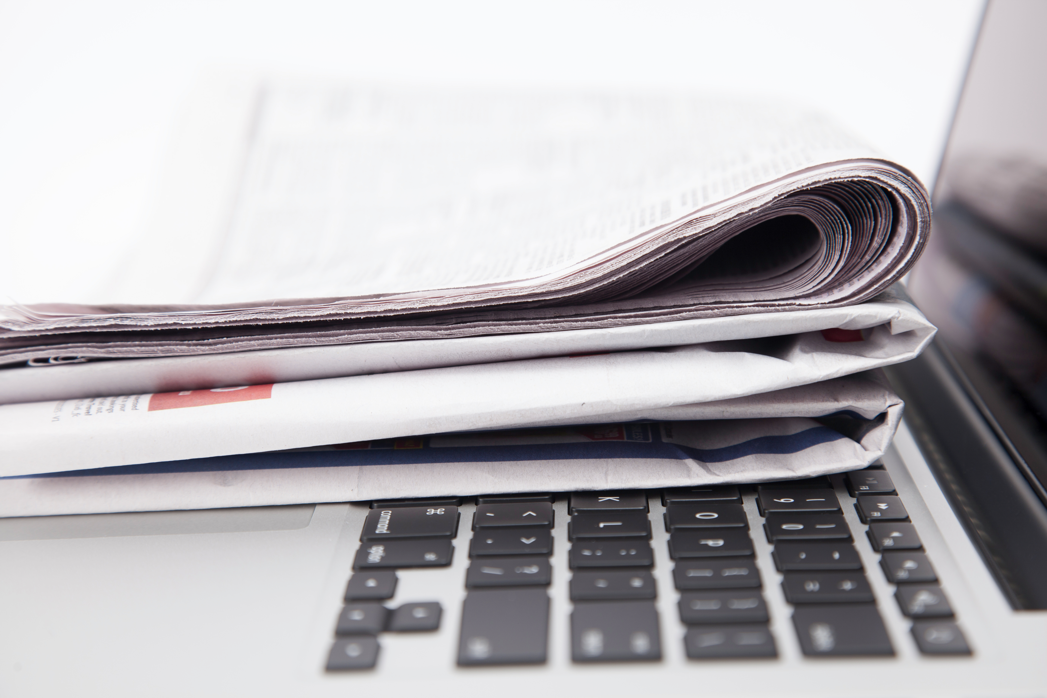 Stack of newspapers resting on laptop keyboard